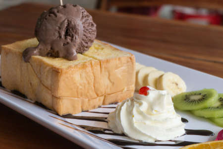Honey Toast bread topped with ice cream, chocolate sevred with fruit and whipped cream,process color Stock Photo