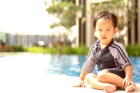 little girl sitting: little girl sitting by swimming pool Stock Photo