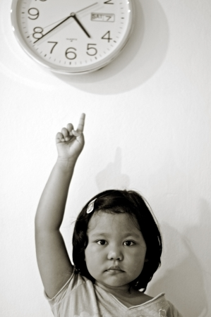 Little girl pointing at clock photo