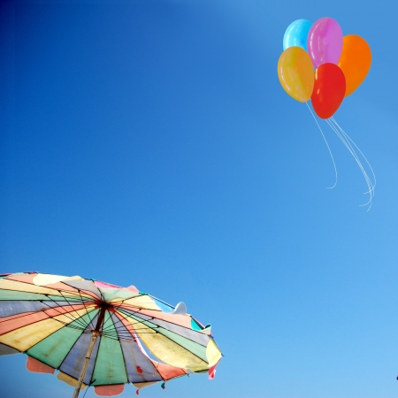 muti: Beach umbrella and colorful balloons against sky