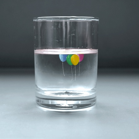 Cool glass of water with colorful balloons photo