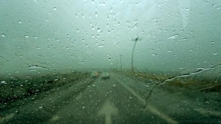Driving in rain with street arrow sign Standard-Bild