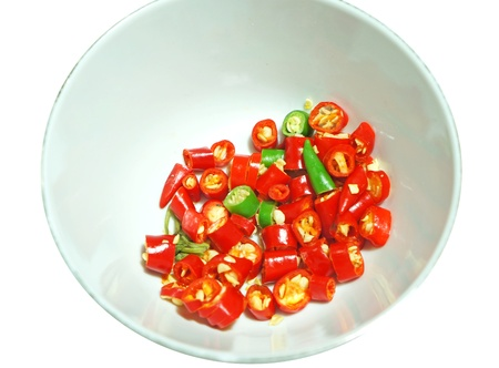 Sliced red chili pepper in small bowl, isolated on white  photo