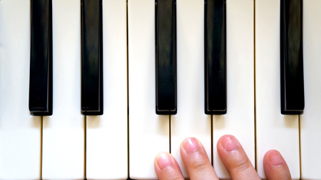 Little hand of girl, playing the piano photo