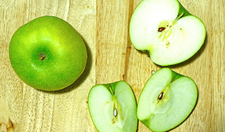 sliced green apple on wooden cutting board photo