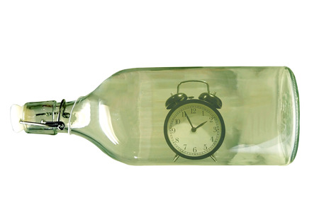 Alarm clock inside an old glass bottle photo