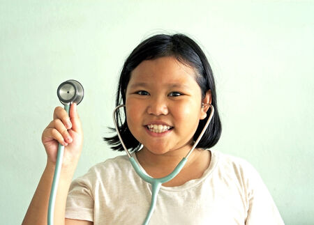 teenager girl pretend to be a doctor  holding stethoscope   photo