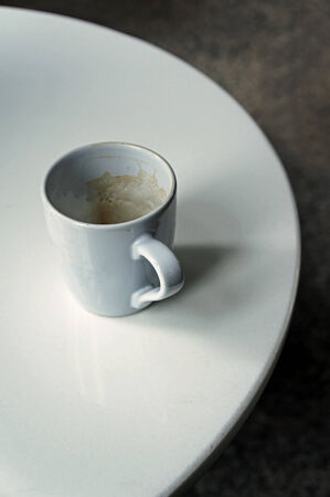 Empty coffee cup on white round table photo