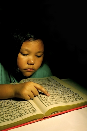 Girl reading arabic book in dark room photo