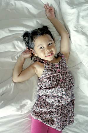 Happy little girl laying in white bed photo