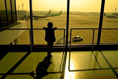 Silhouette of little girl at airport window