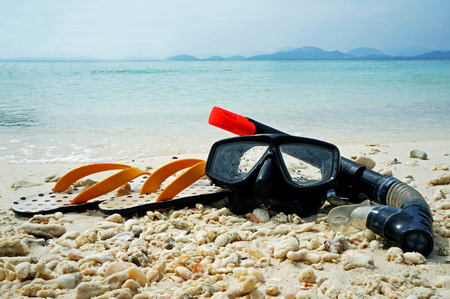 Diving goggles,snorkel and flip flops on sand photo