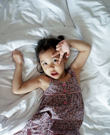 Happy little girl laying in white bedsheet photo