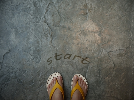 A pair of feet floor with word start for the concept of starting point