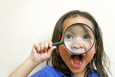 happy funny girl with magnifying glass photo