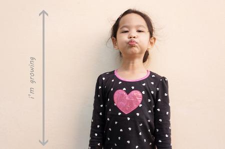 taller: Little girl trying to be taller
