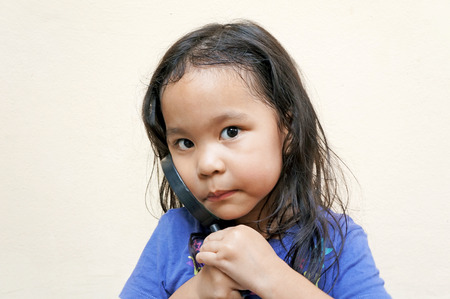 Cute little girl holds magnifying glass photo
