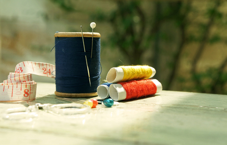 old style image of cotton reels and other sewing items on a wooden table photo