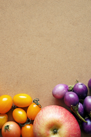 cherry tomatoes and apple on wooden background photo
