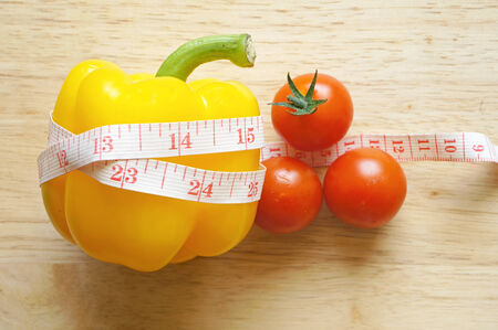 Yellow pepper bell wraping with measuring tape and tomatoes (diet concept) photo