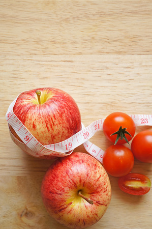 red apple wrapping with tape measure and tomatoes (diet concept) photo