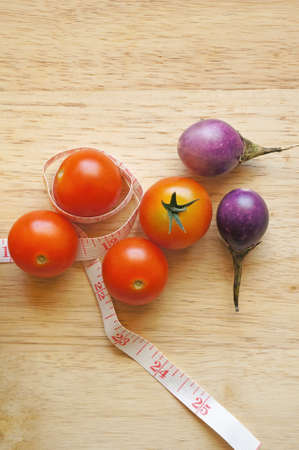 diet concept: cherry tomatoes on wooden background with measuring tape (diet concept)