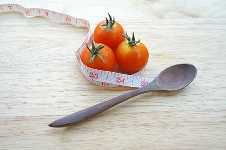 Cherry tomatoes wrapping with measuring tape  diet concept  photo