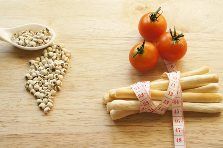 Healthy snack concept, stick biscuit with measuring tape wrapping, millet and tomaotes photo