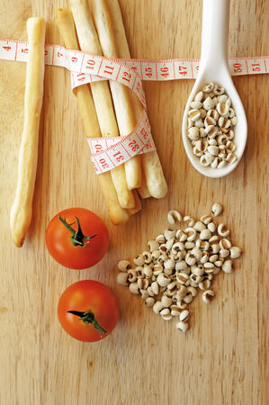 healthy snack: Healthy snack concept, stick biscuits wrapping with measuring tape, millet, tomatoes