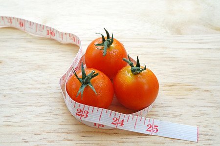 Cherry tomatoes wrapping with measuring tape (diet concept) photo