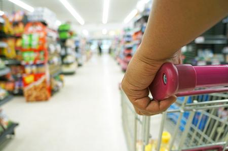 트롤리 또는 쇼핑 카트 쇼핑에서 남자에 근접 촬영 슈퍼마켓 선반 배경에 손에 근접 촬영 스톡 콘텐츠