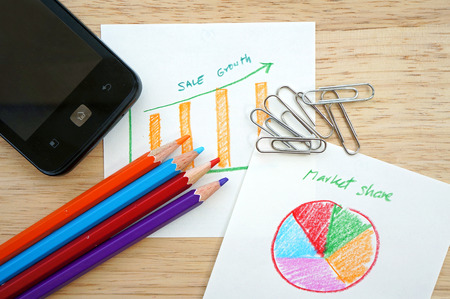 financial gains: Business concept with pencil, paperclip, mobile phone and financial table and graph