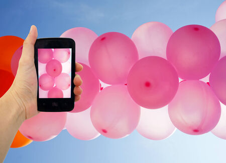 taking pink balloons photo with smart phone photo
