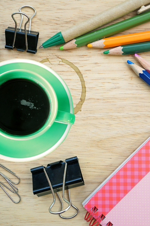 Green coffee cup and office supplies  View from above  Closeup photo