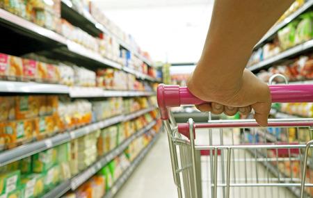 carro supermercado: primer plano la mano en la cesta de la compra en el supermercado