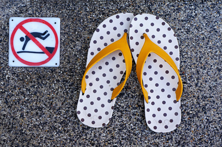 no diving sign: flip flop and a swimming pool with no diving sign Stock Photo