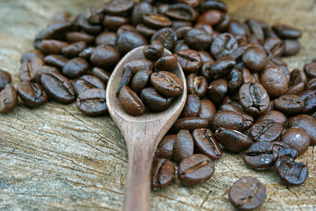 Coffee beans on an old wooden background photo