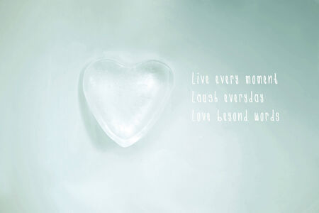 Melting ice heart on a glass surface  Love motto  Stock Photo
