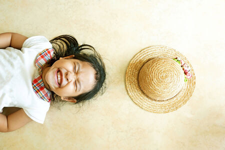Little asian girl laying on the floor with hat photo
