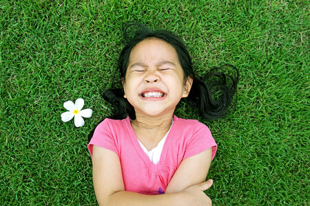 Little asian girl laying in green grass with frangipani flower photo