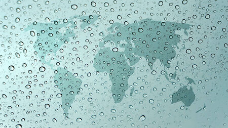 transnational: world map on glass with water drops
