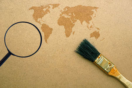 World map, magnifying glass, brush on wooden background photo