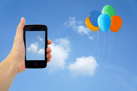Cell phone in hand take photo of beautiful balloon and sky view photo