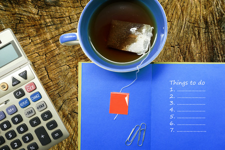 things to do: Office stationery, calculator, coffee cup, notebook with things to do list