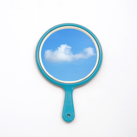 self conceit: hand mirror with reflection of blue sky and cloud isolate on white