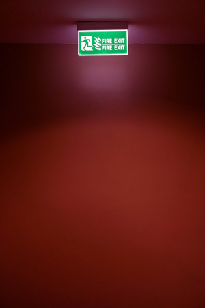 Fire exit board on red wall photo