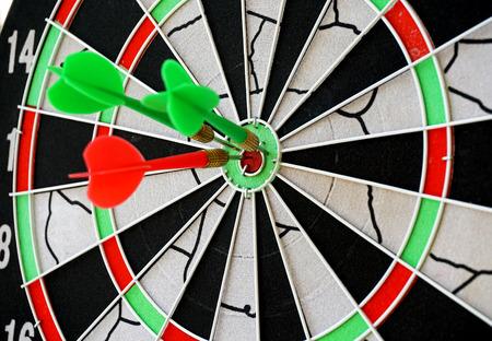 holed: Dart board with darts Stock Photo