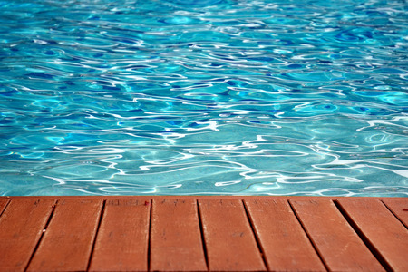 blue swimming pool with wood flooring stripes summer vacation Stockfoto