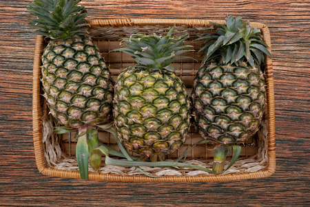 pineapple in basket on wooden background photo