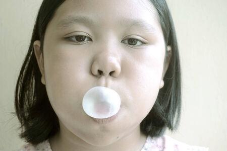 goma de mascar: chica joven hace una burbuja de una goma de mascar (color mon�tono)